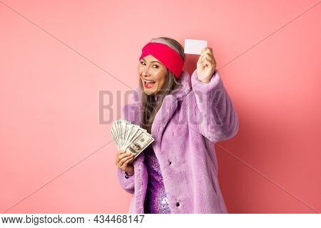 Shopping And Fashion Concept. Fashionable Funky Asian Woman Showing Plastic Credit Card, Paying Cont