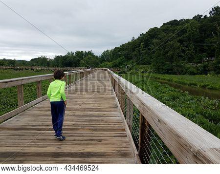 Child On Wood Boardwalk In Wetland With Red Winged Blackbird