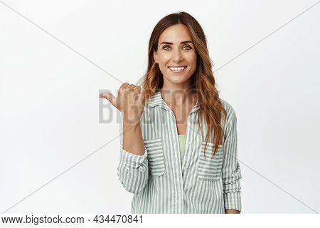 Image Of Confident And Ambitious Brunette Woman Smiling White Teeth, Pointing Finger Left At Logo, S