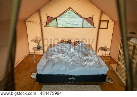 Tired young couple sleeping on large double bed under white sheets in glamping tent