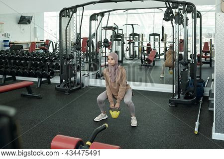 Horizontal long shot of beautiful sporty Muslim woman wearing hijab doing weightlifting exercise with kettlebell in gym