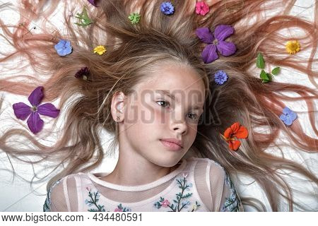 Portrait Of A Beautiful Young Girl With Bright Colorful Flowers And Flower Bud Petals In Beautiful H
