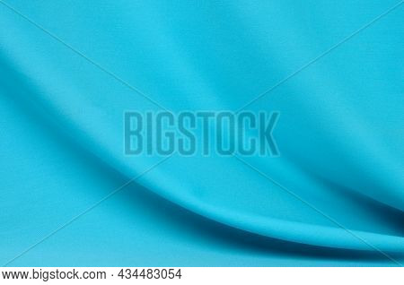 Textured Background Made Of Soft Blue Fabric With Elegant Pleats. Selective Focus.