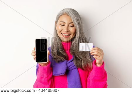 Online Shopping. Closeup Of Fashionable Old Woman Showing Blank Smartphone Screen, Looking Pleased A