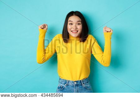 Hopeful Asian Girl Winning Prize, Clench Fists And Smiling Happy At Camera, Triumphing Of Achievemen