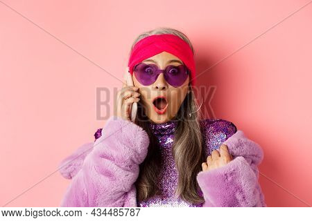 Fashion. Close-up Of Stylish Asian Old Woman Hear Shocking News On Smartphone, Gasping And Staring A