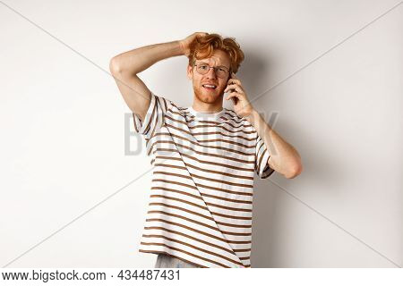 Puzzled Redhead Guy Talking On Phone, Scratching Head And Looking Confused Or Indecisive, Standing O