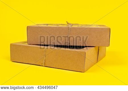 Cardboard Recyclable Boxes Tied With A Eco-friendly Twine, For Storage And Delivery, On Yellow Backg