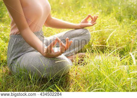 Woman Half Lotus Pose Yoga Meditating On Grass In Park. Breath Determination Keep Calm For Start Doi