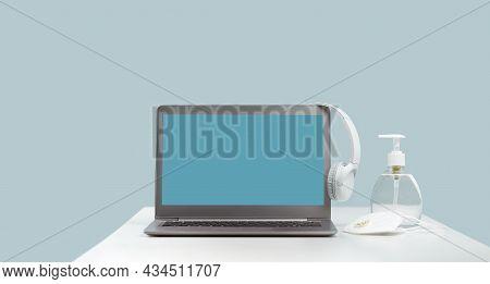 Laptop With Wireless Headphones On White Desk