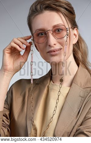 A Beautiful Stylishly Dressed Middle-aged Woman In Stylish Glasses Smiles And Poses At The Camera, A
