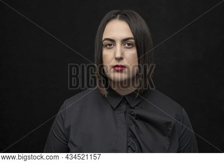 Studio Portrait Of A Plump, Round-faced Woman 30-35 Years Old With Black Hair On A Black Background,