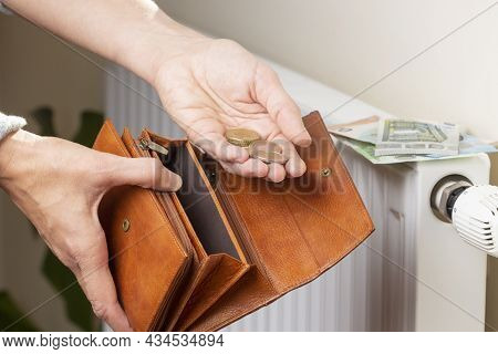 Womans Hand Takes Euro Money From Wallet And Places On Heating Radiator Battery With Temperature Reg