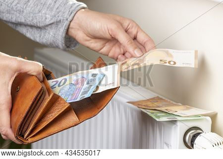 Womans Hand Takes Euro Money Banknotes From Wallet And Places On Heating Radiator Battery With Tempe