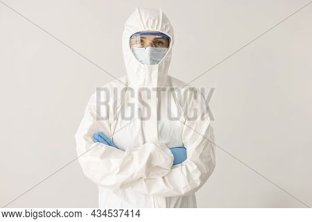 Woman Doctor Or Scientist Stands In Protective Suit, Mask And Glasses With Folded Arms On White Back