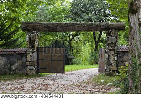 The Wooden Gate In A Stone Wall On A Monastery. Retro Countryside Wooden Gate With With Stone Wall I