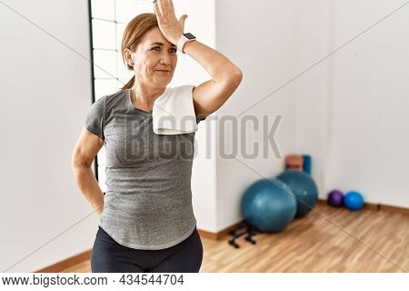 Middle age woman wearing sporty look training at the gym room surprised with hand on head for mistake, remember error. forgot, bad memory concept.