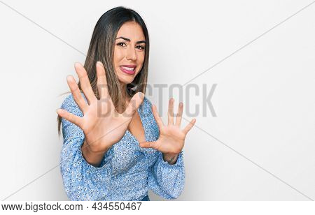 Young hispanic woman wearing casual clothes disgusted expression, displeased and fearful doing disgust face because aversion reaction. with hands raised
