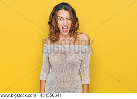 Beautiful young caucasian woman wearing casual clothes winking looking at the camera with sexy expression, cheerful and happy face.