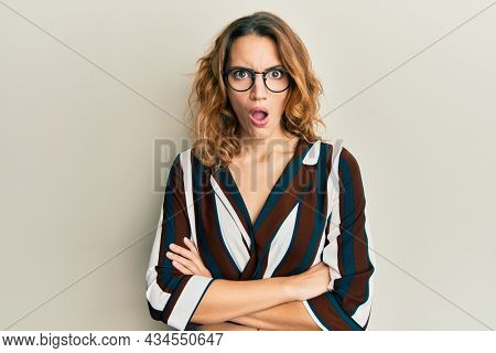 Young caucasian woman wearing business shirt and glasses in shock face, looking skeptical and sarcastic, surprised with open mouth
