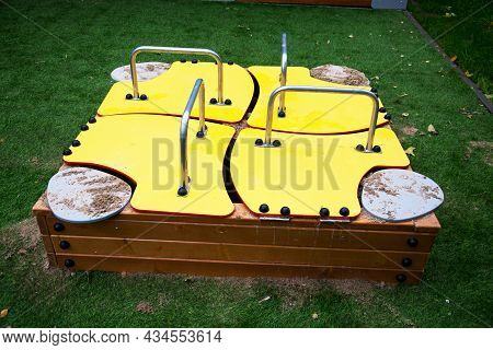 Wooden Sandbox Covered With Bright Yellow Plywood Sheets With Stainless Steel Handles On A Backgroun