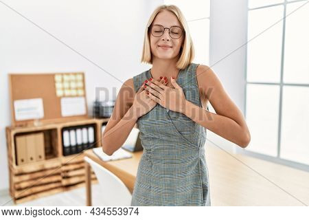 Young caucasian woman working at the office wearing glasses smiling with hands on chest with closed eyes and grateful gesture on face. health concept.