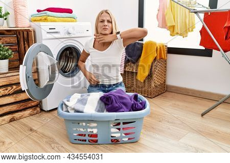 Young caucasian woman doing laundry with clothes in the basket cutting throat with hand as knife, threaten aggression with furious violence