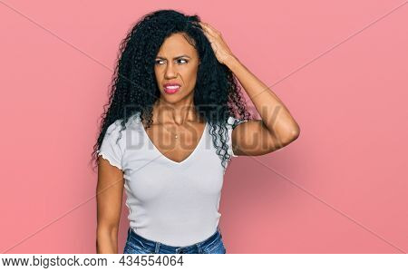 Middle age african american woman wearing casual white t shirt confuse and wonder about question. uncertain with doubt, thinking with hand on head. pensive concept.