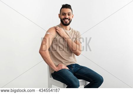 Smiling Vaccinated Arab Man Showing Shoulder With Band Aid After Coronavirus Vaccine Shot, White Stu