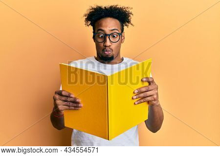 Young african american man with beard reading a book wearing glasses making fish face with mouth and squinting eyes, crazy and comical.