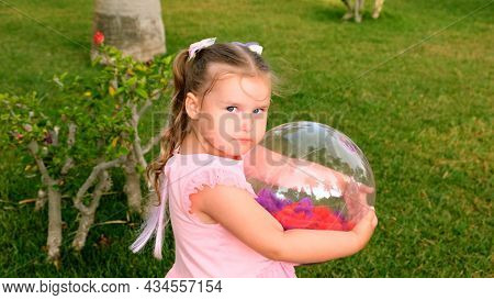 Cute Little Girl, 3 Years Old, With Two Ponytails On Her Head, Dressed In A Delicate And Multi-color