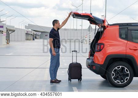 A Person With Luggage Opens The Trunk Of A Car In The Parking Lot