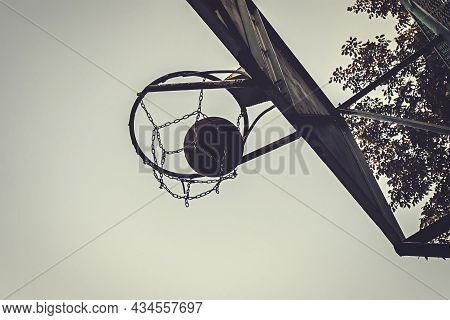 Basketball Ball Passing Through A Metal Hoop Outdoors