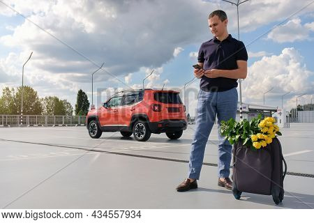 A Young Man Using A Phone In His Hands With A Suitcase And Flowers In The Parking Lot, Waiting For A