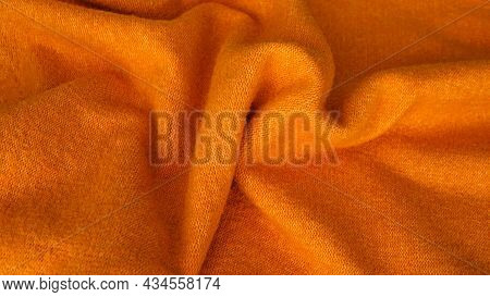 Background With Wavy Lines From Natural Silk Fabric. Orange Fabric Background. Silk Fabric Backgroun