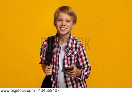 Happy Calm Caucasian Teen Boy Pupil With Backpack And Smartphone Ready To Learn, Chatting With Frien