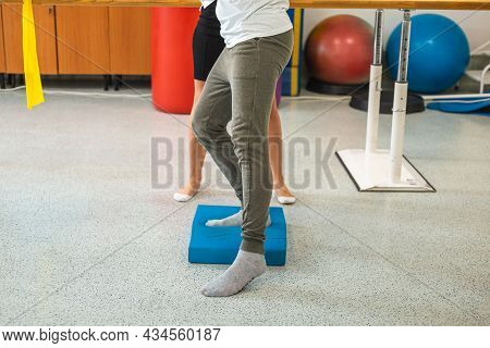 Male Patients Legs Doing Balance Pad Exercises With The Assistance Of A Female Therapist.