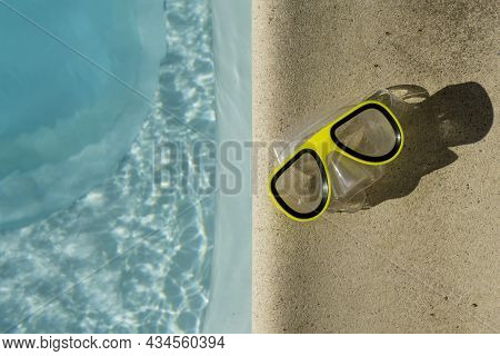 Yellow Swimming Goggles Next To A Clear Blue Rippled Swimming Pool