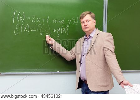 A Strict Math Teacher At The Blackboard Explains The Solution Of The Problem To Students.