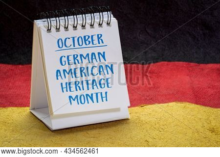 October - German American Heritage Month, handwriting in a small desktop calendar against paper abstract in colors of Germany national flag, reminder of cultural event