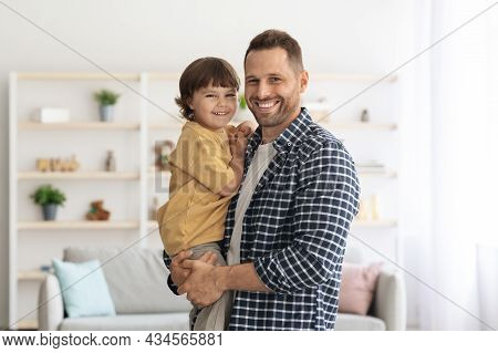 Young Happy Father Carrying His Beloved Little Son On Hands And Bonding, Smiling Together To Camera