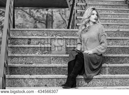 Woman With Gorgeous Hairstyle Sit On Stairs Outdoors. Fall Fashion Trend. Layer Oversize Knit Over G