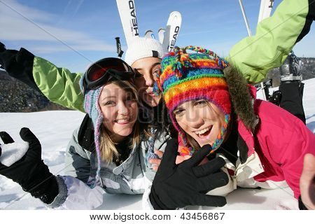 Three friends laying in the snow with ski equipment