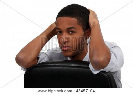 Bored young businessman sat on office chair