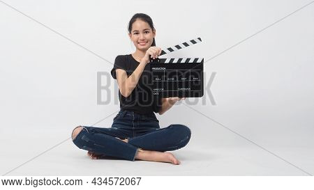 Asian Young Woman Holding Black Clapper Board Or Movie Slate Or Clapboard And Sit On The Floor .it U