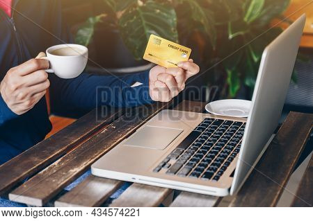 Cropped Shot Of Woman Hand Holding A Cup Of Hot Coffee While Doing Shopping Online And Payment By Cr