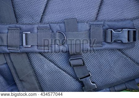 One Large Black Fabric Harness With Metal Rings And Plastic Carabiners On A Tactical Backpack