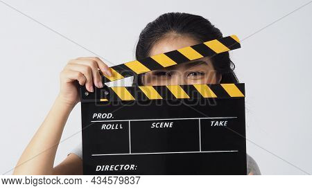Asian Woman With Smiling Eyes Eye And Wear Contact Lenses .hand's Holding Black Clapper Board Coverd