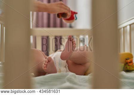 Closeup View Lovely Babys Barefeet Through Crib Bars View. Selective Focus On Cute Feet Among Defocu