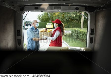 Delivery Man With Protection Mask Delivering Food To The Senior Man During Covid19 Pandemic Or Lockd
